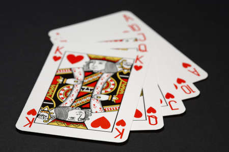 Royal flush poker combination - closeup of playing cards: king, queen, jack, ten and ace. Shallow focus depth on front sides of cards