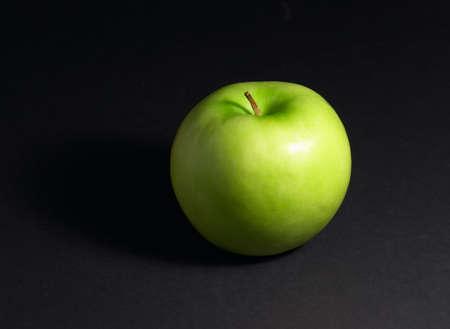 Green apple on black background with small shadow Zdjęcie Seryjne