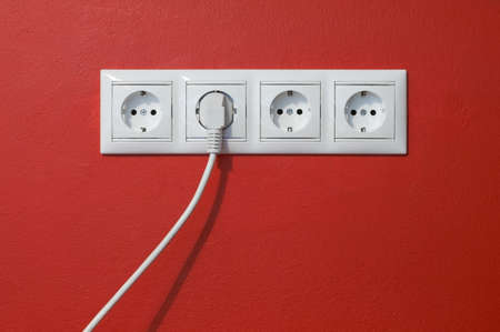 Electrical outlets, cable and electric plug on red textured wall