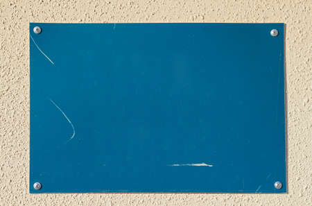Closeup of empty blue board on beige concrete wall - The empty space for something
