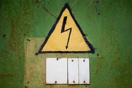 Yellow high voltage sign on aged green textured wall - Empty white sign board below for some text