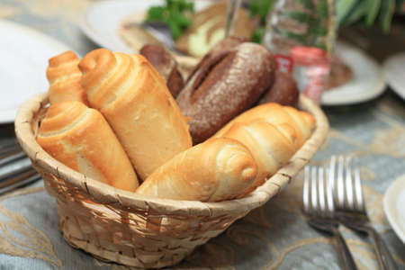 Closeup of white and rye bread rolls in basket on restaurant table. Shallow focus depth on near rolls