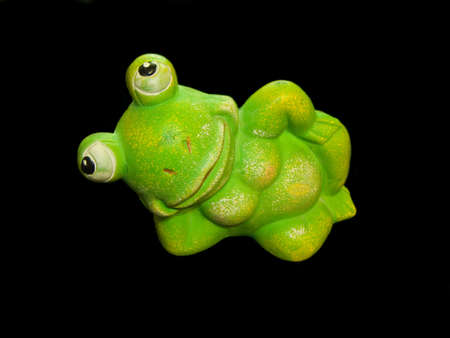 An isolated on black photo of a green frog photo
