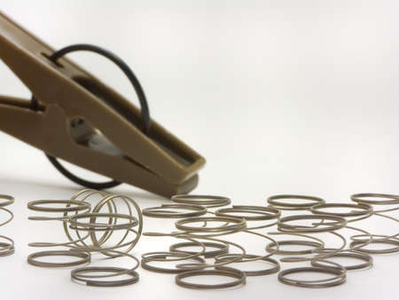 An isolated close-up photo of several springs and a clip for clothes photo