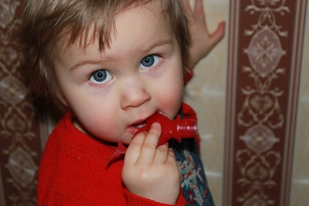 girl licks a toy Stock Photo