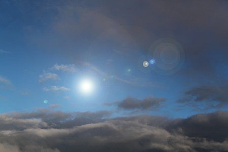 Fluffy horizontal grey clouds and sun shine between them Stock Photo - 9626538
