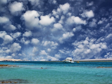 Coastline of the red sea: sea and fluffy clouds