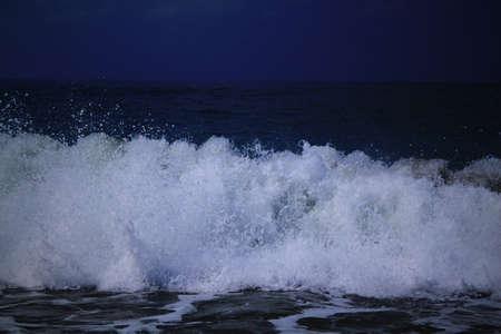 Las olas y las salpicaduras en la noche. Mar del paisaje. Chipre