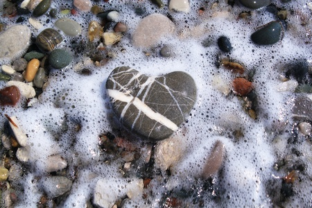 Stone heart on color pebbles photo