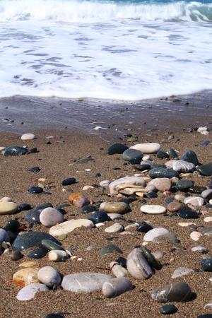 Piedras de color en una playa de arena. Chipre Foto de archivo