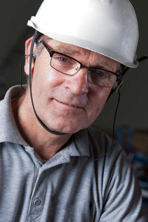 portrait of a happy engineer with safety helmet, earplugs and safety glasses