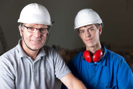 portrait of a happy senior and junior engineer with safety helmet, earplugs and glasses