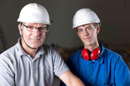 Portret van een gelukkig senior en junior ingenieur met veiligheidshelm, oordopjes en glazen Stockfoto