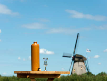 A bottle and a glas of jenever in front of a typical Dutch landscape