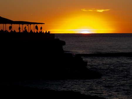 Zonsondergang gezien vanuit het ZW van Ibiza met een beachclub op de voorgrond