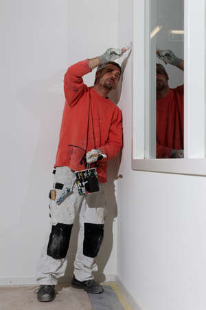 Painter on the job. Painting the inside of a new factory building with an office
