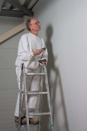 contracting: painter filling up a wall with filler, looking carefully not to forget a hole or scratch
