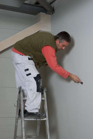 painter filling up a wall with filler, looking carefully not to forget a hole or scratch
