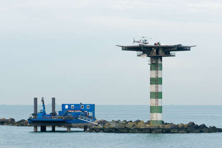 heliport: The entrance of a commercial harbor with a flightdeck on top