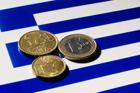 greek coins: A few Euro coins on top of the Greek  flag