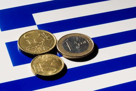 crisis economica: A pocas monedas de euro en la parte superior de la bandera griega