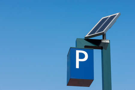 Solar cells generating electricity for a parking meter against a blue sky Stock Photo