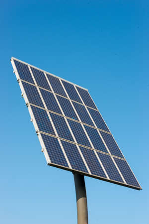 Solar cells generating electricity against a blue sky photo