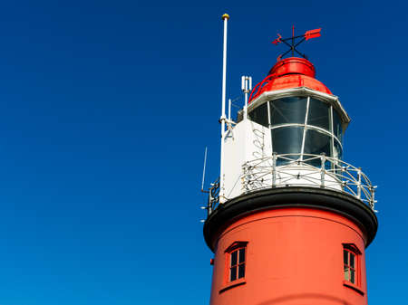 red lighthouse against a clear blue sky photo