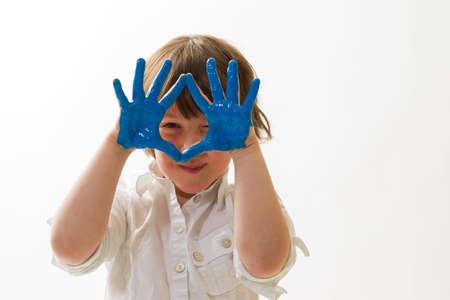 child with paint on the hands in front of a white background photo