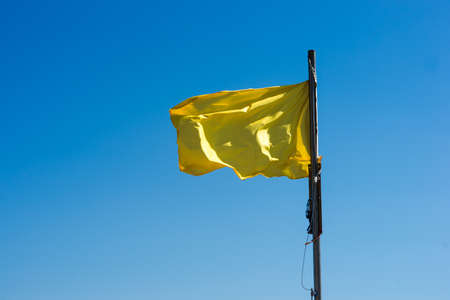 yellow flag as a warning sign on a beach photo