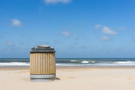 A garbage container on a clean beach photo