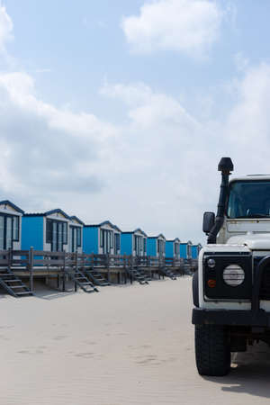 Blue cabanas for rent on a sandy beach with a 4x4 in the foreground Stock Photo - 14354096