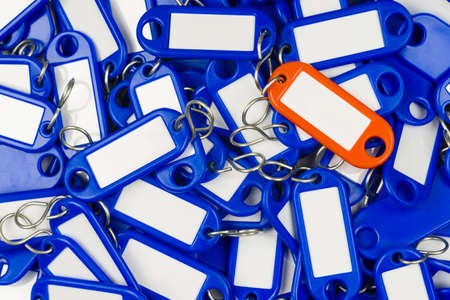 many blue and a single orange plastic key tag Stock Photo - 16847719
