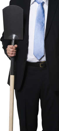Executive showing a spade as a metaphor for digging, hard work and earth moving Stock Photo - 16928144