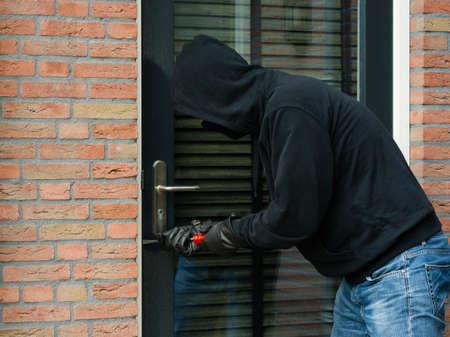 Burglar using a screwdriver as a crowbar