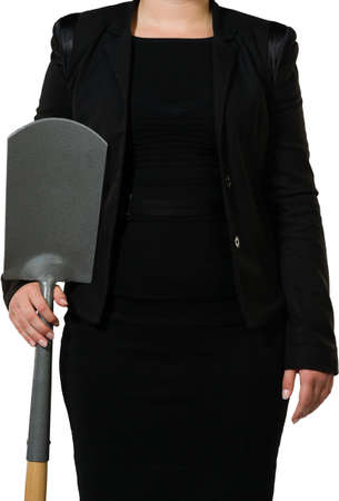 Female executive showing a spade as a metaphor for digging, hard work and earth moving Stock Photo