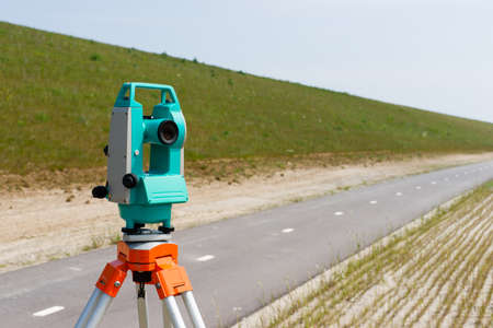 A modern theodolite or total station on a tripod  Stock Photo