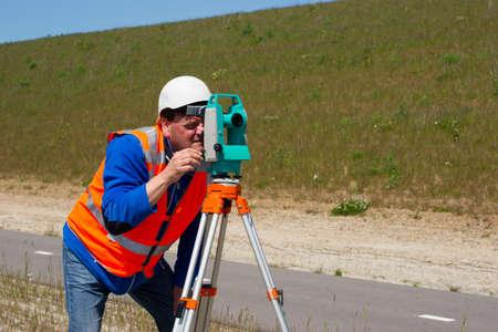 surveyor: Ingeniero trabajando con un teodolito moderno o estaci?n total en un tr?pode