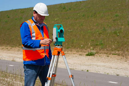 tachymeter: Engineer working with a modern theodolite or total station on a tripod