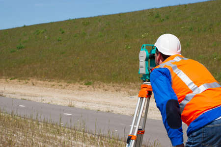 Engineer working with a modern theodolite or total station on a tripod  photo