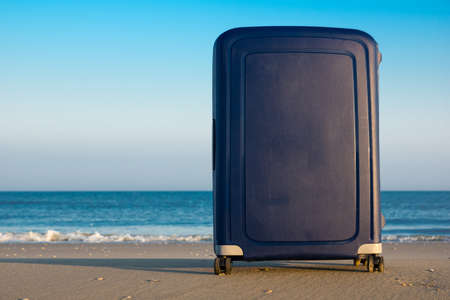 A blue suitcase on an empty beach with a quiet waterline and hardly any waves