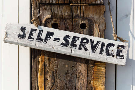 oaken: hand written self-service sign on a weathered oaken pole Stock Photo