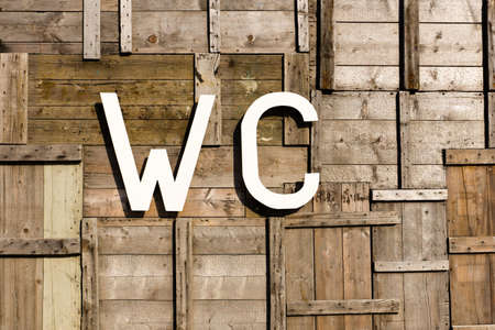 a wc sign with a background of vintage weathered wood photo