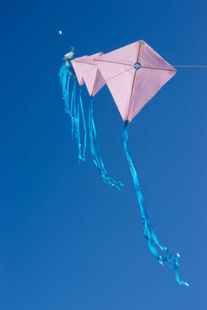 Multiple kites on a row against a blue sky