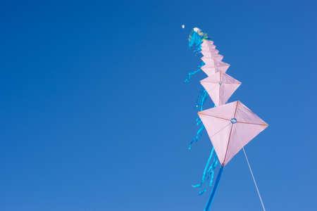 Multiple kites on a row against a blue sky