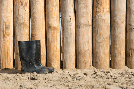 weathered wood on beach and a pair of rubber boots