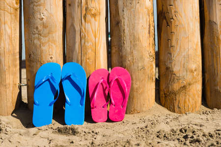 weathered wood on the beach and some slippers photo