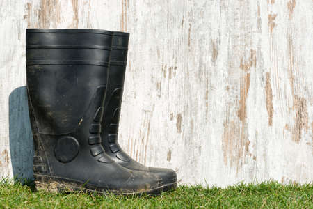 weathered wood on a field of grass and a pair of rubber boots Stock Photo