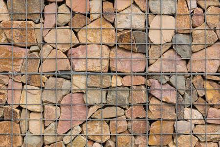 diverse stenen zorgvuldig aranged in een ijzeren net om een muur te maken