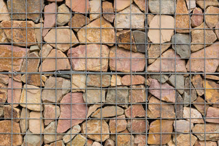various stones carefully aranged in an iron net to make  a wall